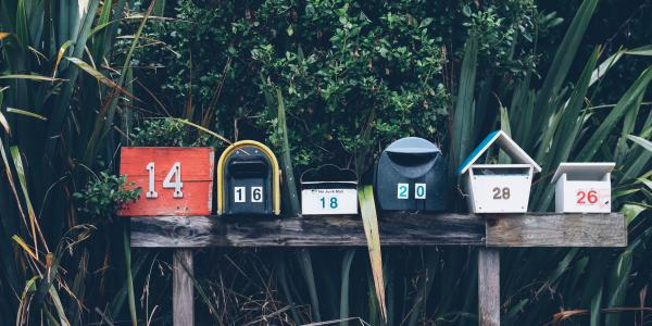 a row of six multicolored mailboxes